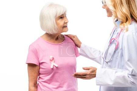 Doctor embracing senior woman with pink ribbon of breast cancer awareness isolated on white