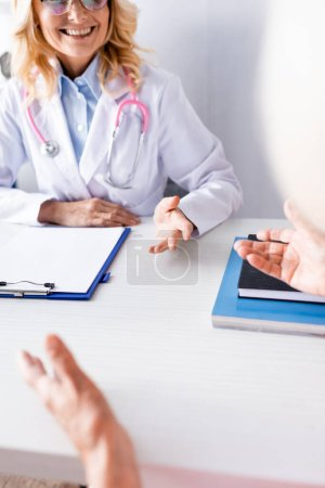 Selective focus of doctor with stethoscope sitting at table near clipboard