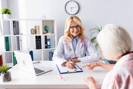 Photo pour Concentration sélective de l'écriture du médecin sur le presse-papiers et de regarder le patient à la clinique - image libre de droit
