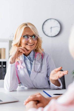 Photo pour Concentration sélective du médecin avec ruban rose regardant loin tout en étant assis à la table - image libre de droit