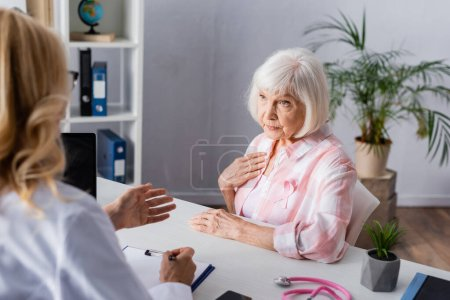 Photo for Selective focus of elderly woman with pink ribbon sitting near doctor in clinic - Royalty Free Image