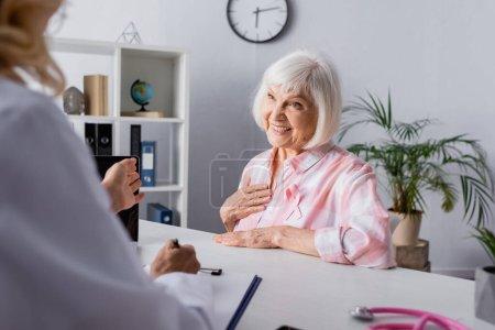 Photo pour Concentration sélective de la femme âgée avec la main sur le sein assis devant le médecin - image libre de droit