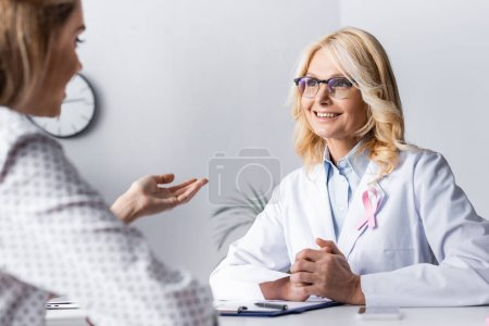 Photo for Selective focus of doctor with clenched hands sitting near patient at workplace - Royalty Free Image
