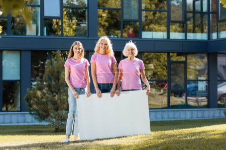 Three women in pink t-shirts with empty board, concept of breast cancer