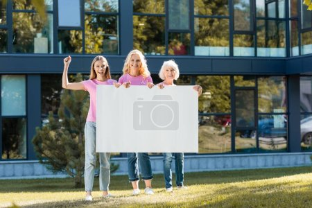 Photo for Young adult woman with yes gesture standing near women with blank placard outdoors - Royalty Free Image