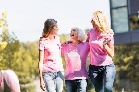 Photo pour Trois femmes s'embrassant et se regardant à l'extérieur, concept de cancer du sein - image libre de droit