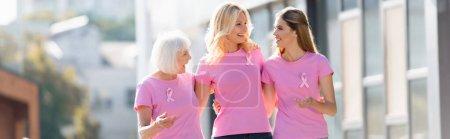 Foto panorámica de mujeres con cintas rosadas de conciencia sobre el cáncer de mama al aire libre