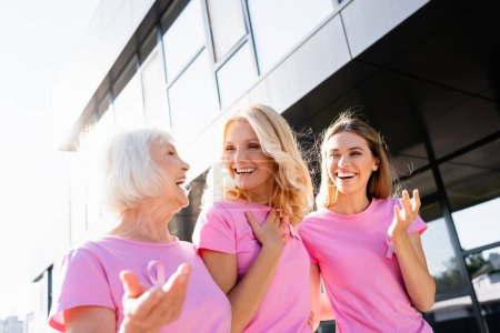 Women in pink t-shirts laughing and hugging outdoors, concept of breast cancer