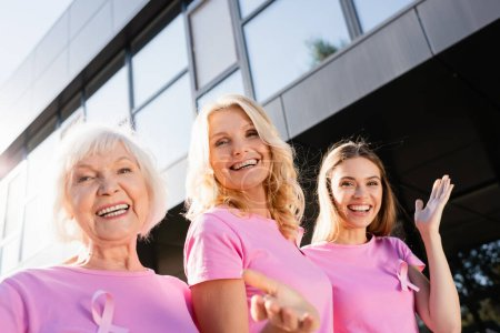 Women with signs of breast cancer awareness hugging and looking at camera