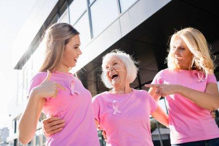 Foto de Mujeres riendo y señalando con los dedos a la señal de la conciencia del cáncer de mama - Imagen libre de derechos