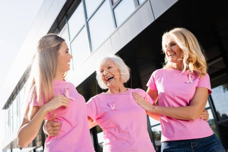 Three women hugging and laughing with signs of breast cancer awareness outdoors