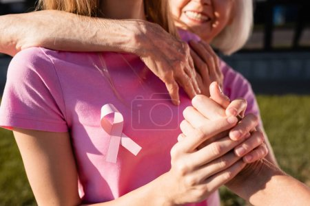 Selective focus of women embracing and holding hand outdoors