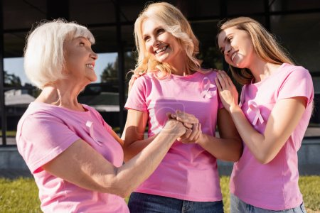 Photo for Three women in pink t-shirts standing together, looking at each other outdoors - Royalty Free Image