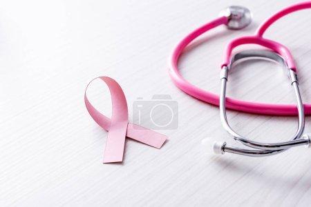 Photo pour Ruban rose de sensibilisation au cancer du sein près du stéthoscope sur fond de bois blanc - image libre de droit