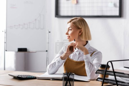 Blonde businesswoman looking away while sitting at desk with stationary in office on blurred background