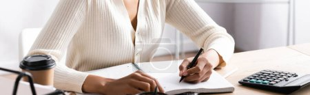 Photo pour Vue recadrée d'une femme afro-américaine écrivant sur un carnet vierge alors qu'elle était assise au bureau sur un fond flou, bannière - image libre de droit