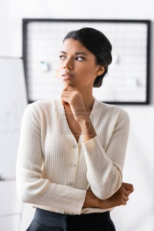 Photo for Thoughtful african american woman with hand near chin looking away while standing in office on blurred background - Royalty Free Image