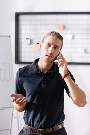Selbstbewusster Geschäftsmann gestikuliert beim Telefonieren im Büro vor verschwommenem Hintergrund