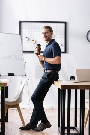 Photo pour Travailleur de bureau souriant avec tasse en papier regardant la caméra, tout en s'appuyant sur la table dans le bureau - image libre de droit