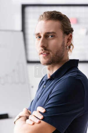 Confident young adult man with crossed arms looking at camera at workplace on blurred background