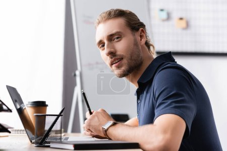 Confident office worker looking at camera while sitting near laptop at workplace table on blurred background