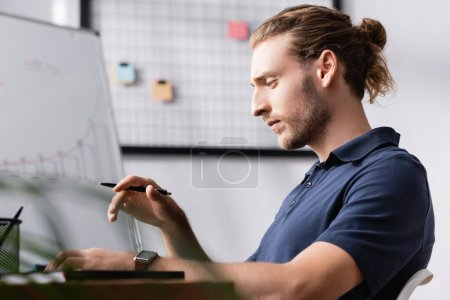 Thoughtful office worker with pen looking away while sitting at workplace desk with blurred plant on foreground