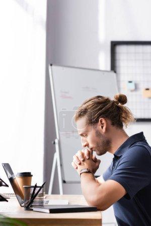 Nachdenkliche Büroangestellte mit geballten Händen am Arbeitstisch neben Laptop auf verschwommenem Hintergrund