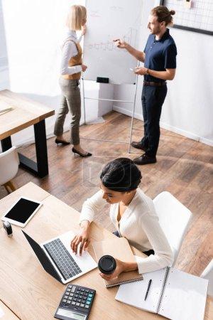 Photo pour Vue aérienne de la femme afro-américaine utilisant un ordinateur portable alors qu'elle était assise à table avec des employés de bureau parlant en arrière-plan - image libre de droit