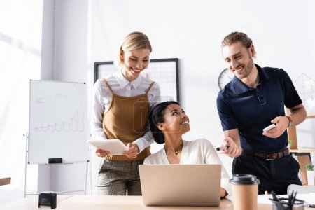 Happy office workers standing near african american woman sitting at table with laptop at workplace