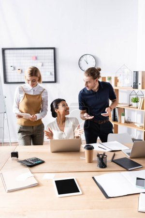 Photo pour Travailleurs de bureau heureux gestuelle tandis que debout près de femme afro-américaine assis sur le lieu de travail avec de la papeterie - image libre de droit