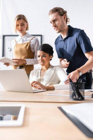 Skeptische Büroangestellte stehen neben einer Afroamerikanerin und schauen auf den Laptop auf dem Tisch mit verschwommenem Briefpapier im Vordergrund