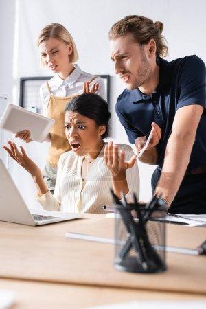 Ofendidos trabajadores de oficinas multiculturales haciendo gestos mientras miran a la computadora portátil en el lugar de trabajo con plumas borrosas en primer plano