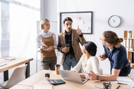 Multicultural office workers looking at excited colleague with idea gesture while standing in office near workplaces