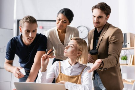 Photo for Blonde woman looking away while sitting at table with skeptical, multicultural office workers standing behind and looking at laptop at workplace - Royalty Free Image