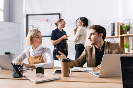 Photo for Man gesturing while talking to blonde woman sitting at table with smiling, multicultural office workers on background - Royalty Free Image