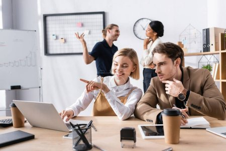 Photo for Focused man sitting at workplace near woman pointing with finger, while using laptop with multicultural office workers on background - Royalty Free Image