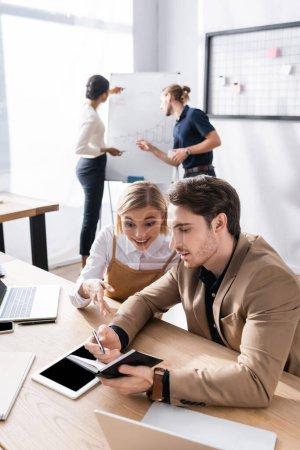 Mujer emocionada mirando el cuaderno en la mano del hombre sentado en el lugar de trabajo en la oficina, con colegas difusos multiculturales en el fondo