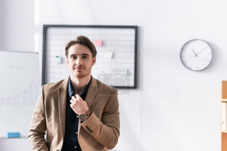 Smiling businessman looking at camera while touching collar of shirt in office on blurred background