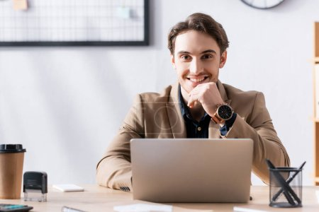Smiling office worker looking at camera while sitting near laptop at desk in office on blurred background