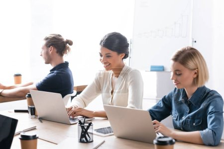 Smiling multicultural female co-workers typing on laptops while sitting at desk near colleague in office