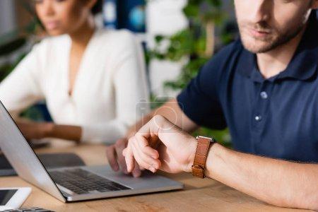 Photo pour Vue recadrée d'un employé de bureau regardant la montre, tout en utilisant un ordinateur portable au bureau avec une femme afro-américaine floue sur fond - image libre de droit