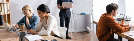 Man holding laptop and standing near multicultural colleagues sitting at workplaces in office, banner