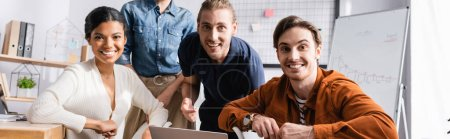 young, cheerful multicultural businesspeople smiling at camera together, banner