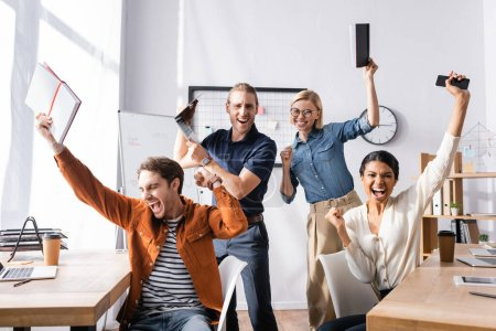 excited multicultural businesspeople shouting and showing success gesture in office