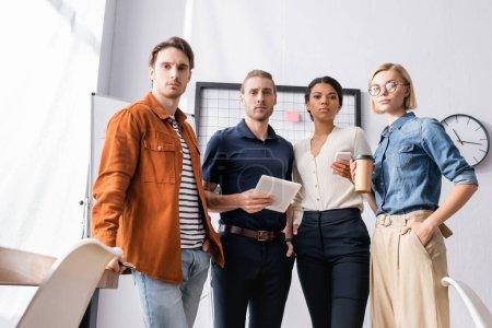 Photo pour Confiants, jeunes entrepreneurs multiculturels regardant la caméra tout en tenant des gadgets et du café à emporter - image libre de droit