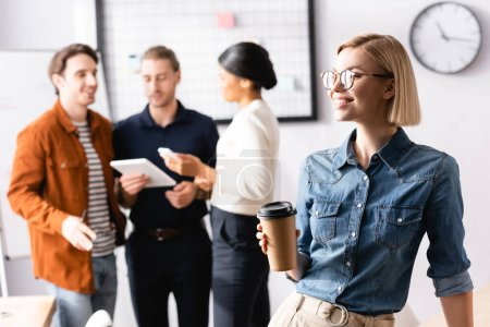 Photo for Young, cheerful businesswoman in eyeglasses holding coffee to go while multicultural colleagues talking on blurred background - Royalty Free Image