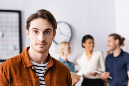 young manager looking at camera while multiethnic businesspeople discussing project on blurred background