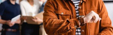 Photo pour Vue recadrée du gestionnaire regardant la montre-bracelet près de collègues flous en arrière-plan, bannière - image libre de droit