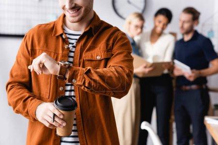 Foto de Sonriente hombre de negocios sosteniendo café para ir y mirando reloj de pulsera cerca de colegas hablando sobre fondo borroso - Imagen libre de derechos