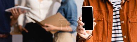 Photo pour Vue partielle de l'homme d'affaires montrant smartphone avec écran vide près de collègues flous en arrière-plan, bannière - image libre de droit